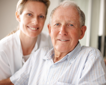 Closeup of a happy retired man on the wheel chair with a nurse